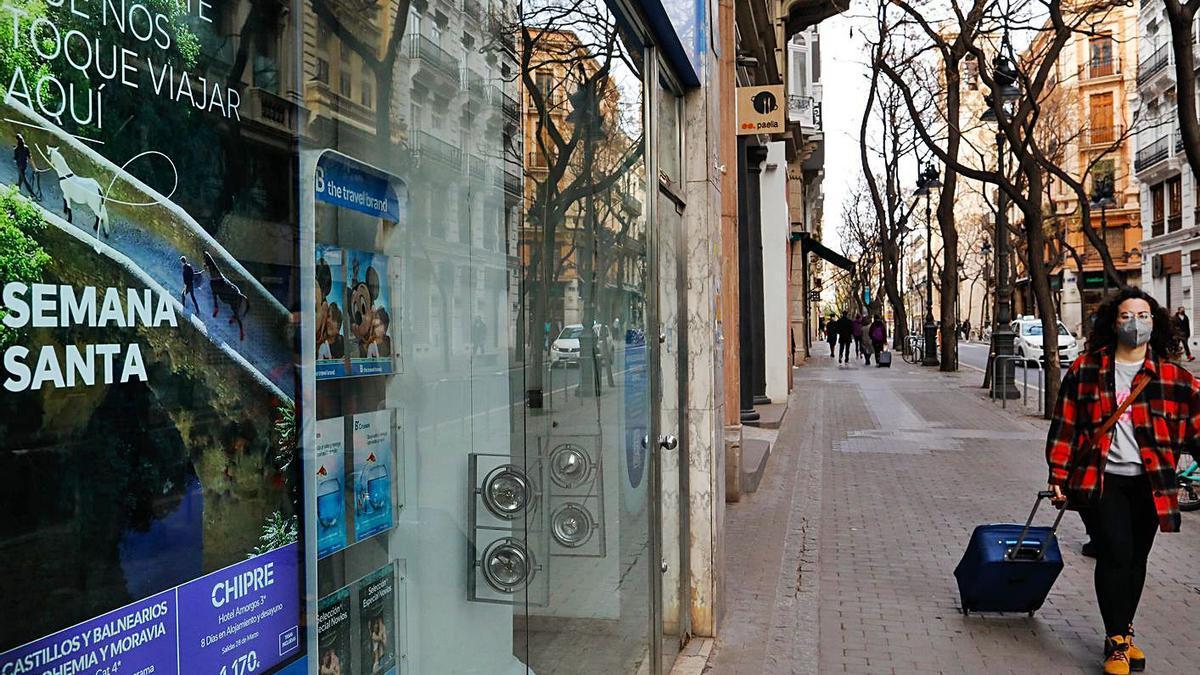 Una chica pasa por una agencia que promociona viajes de Semana Santa, ayer en València. | M. A. MONTESINOS