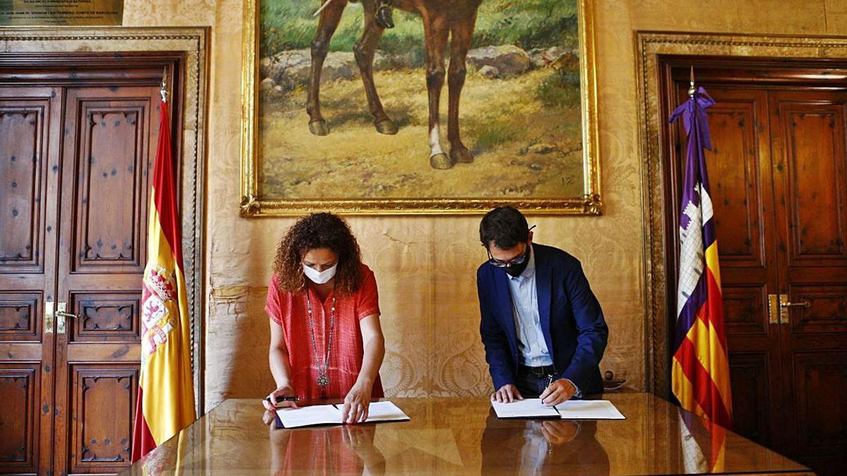 La presidenta insular, Catalina Cladera, y el conseller Negueruela sellan el convenio.  | CAIB
