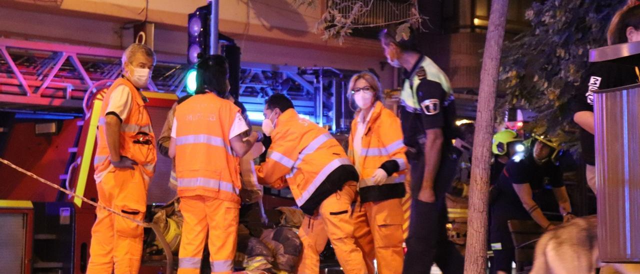 Los servicios sanitarios atienden a un bombero en el lugar del incendio en Alicante.