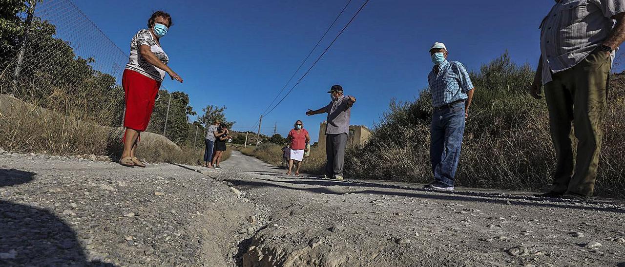 Socavones en el camino afectado, y enseres tirados junto un contenedor roto en la zona.