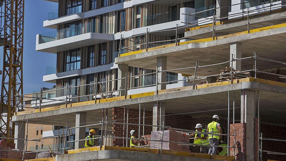 Operarios de la construcción trabajando en los forjados de un edificio en Playa de San Juan.