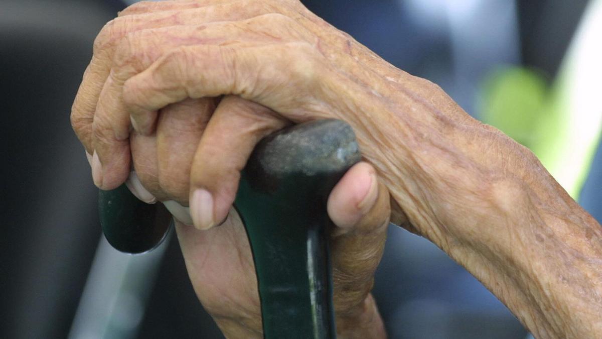 Las manos de una señora mayor sujetando un bastón.