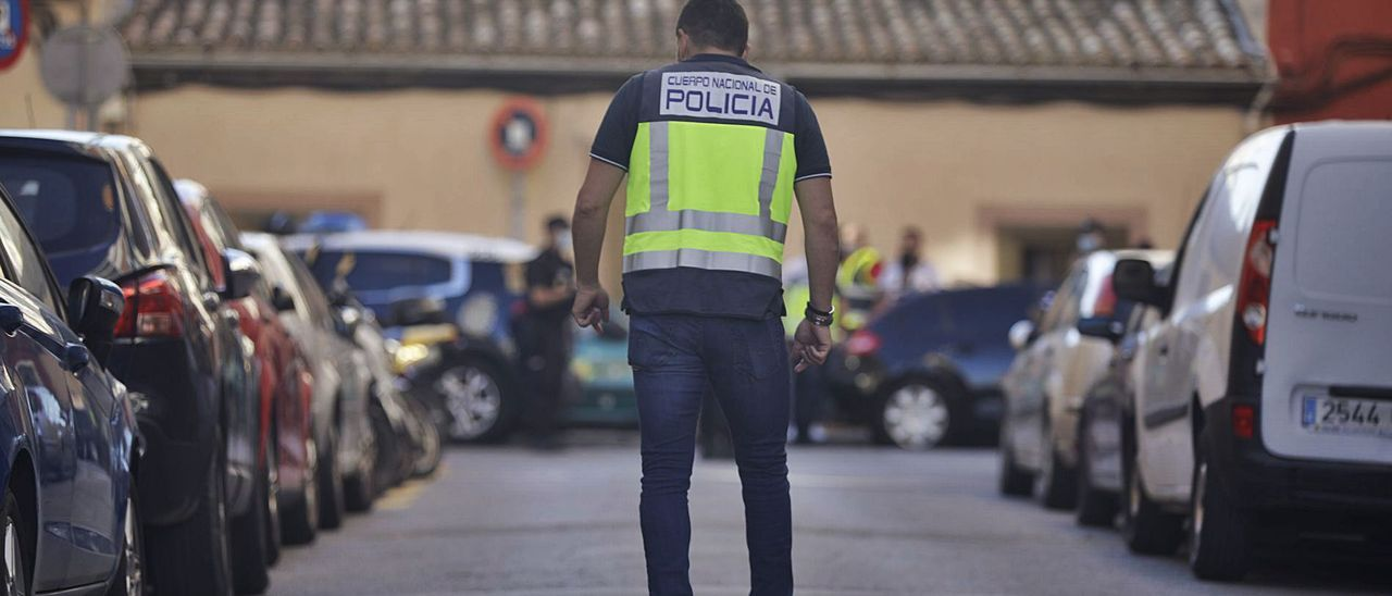 Un agente de la Policía Nacional examina la calle Sant Fulgenci en busca de casquillos de bala tras un tiroteo entre clanes.
