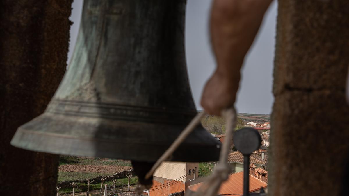 Un hombre toca una campana en un puelbo.