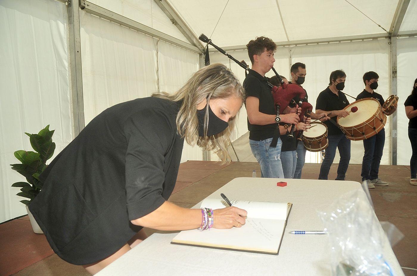 Teresa Portela firma en el libro del Concello, con el grupo Tromentelo al fondo. Rafa Vázquez.jpg