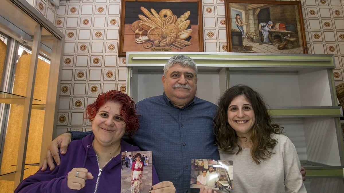 Baltasar y sus hijas, una de ellas con al foto de su madre.