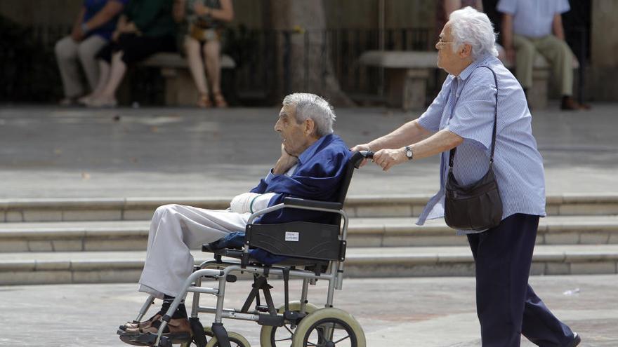 Un anciano lleva a otro en silla de ruedas.