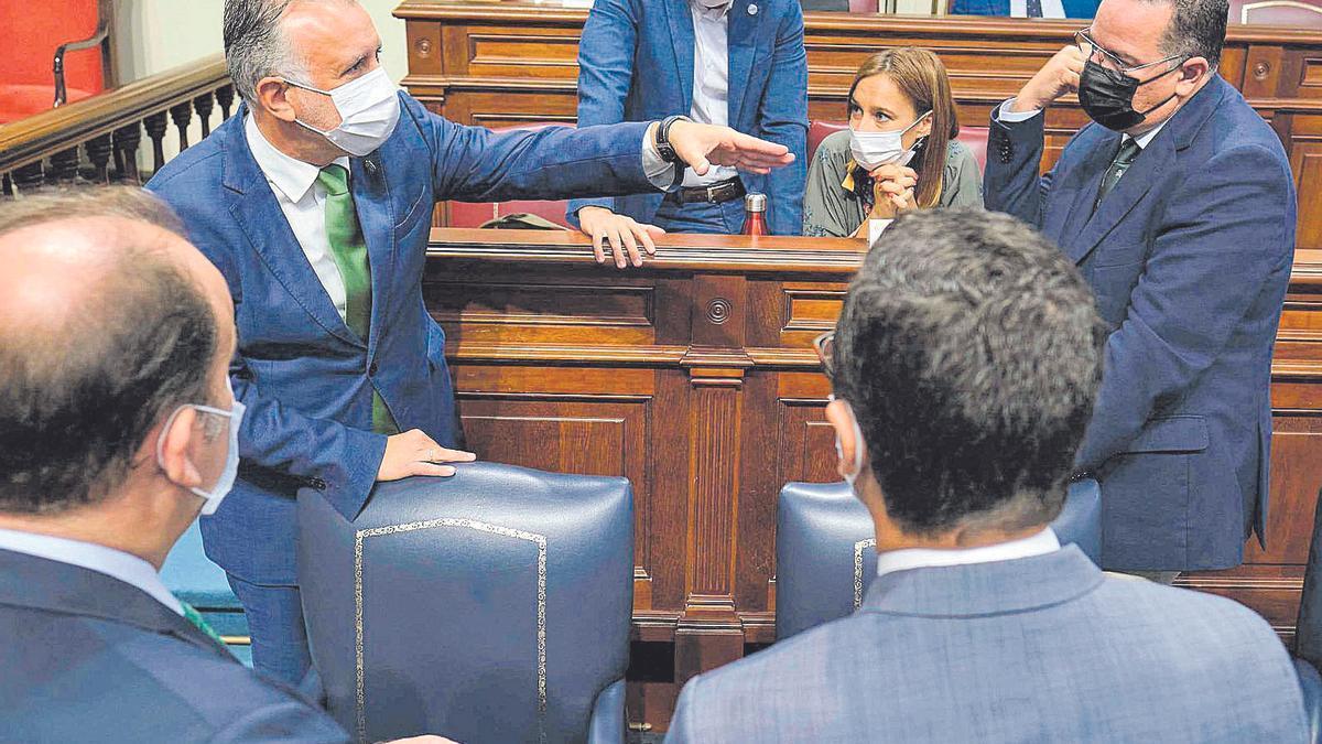 Ángel Víctor Torres hablando ayer en el pleno del Parlamento canario con otros diputados.