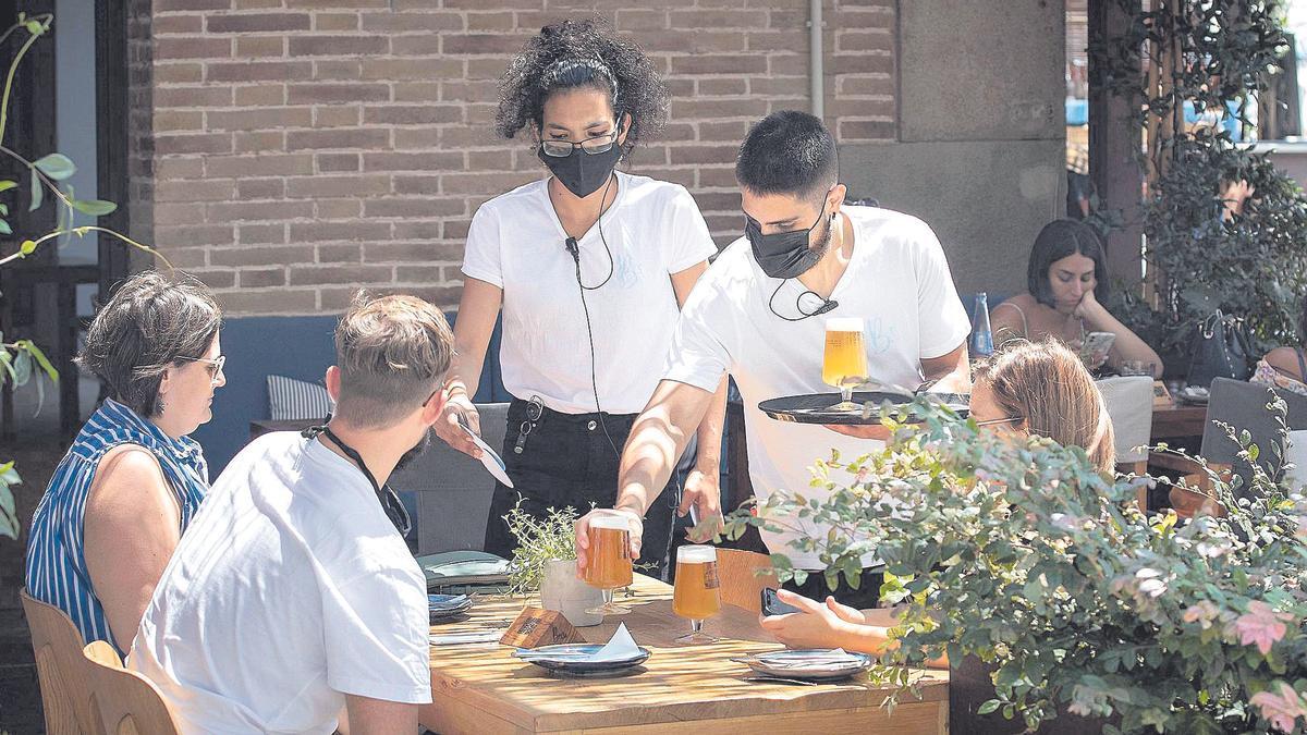 Dos jóvenes sirven unos refrescos en la terraza de una cafetería.