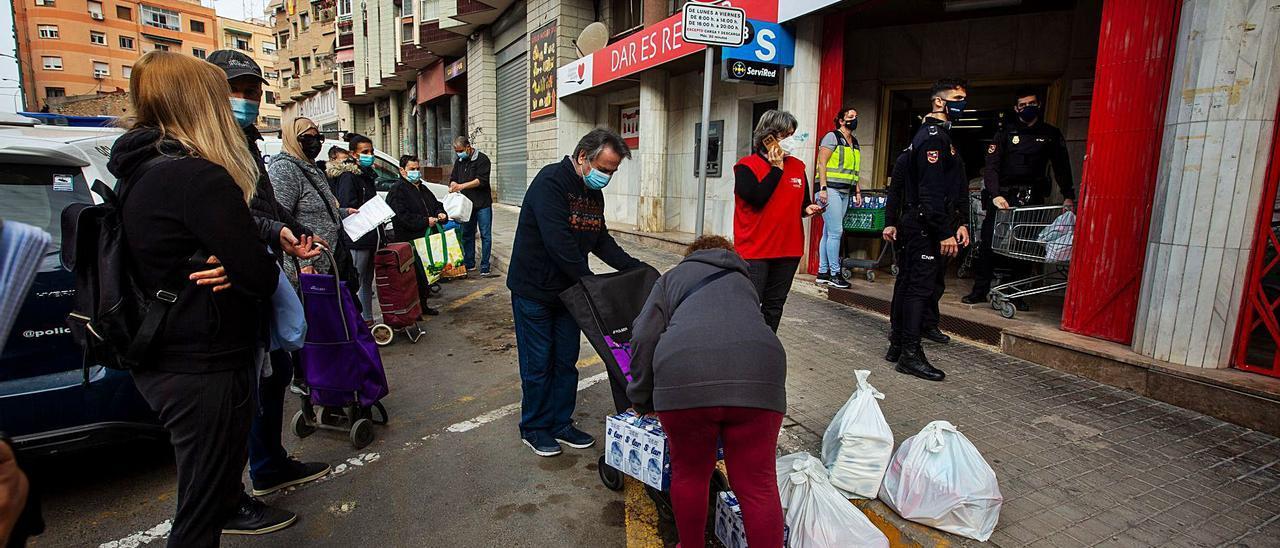 Un grupo de personas hace cola para recoger alimentos durante la pandemia en Alicante. | INFORMACIÓN