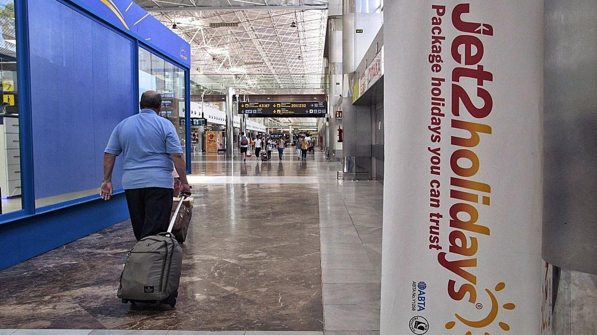 Un viajero pasa frente a un mostrador de la aerolínea y turoperador Jet2 en el aeropuerto de Tenerife Sur, mucho más vacío de lo habitual por el coronavirus.