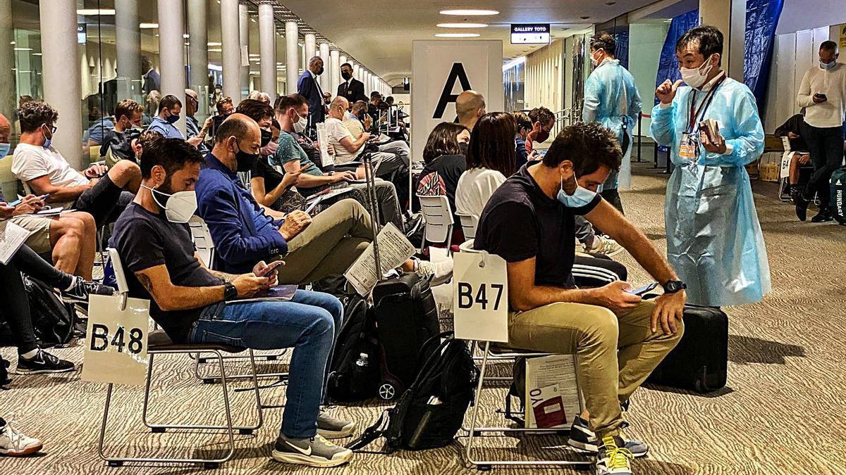 Periodistas y deportistas esperan en el aeropuerto a que se les autorice a entrar en el país. // REUTERS