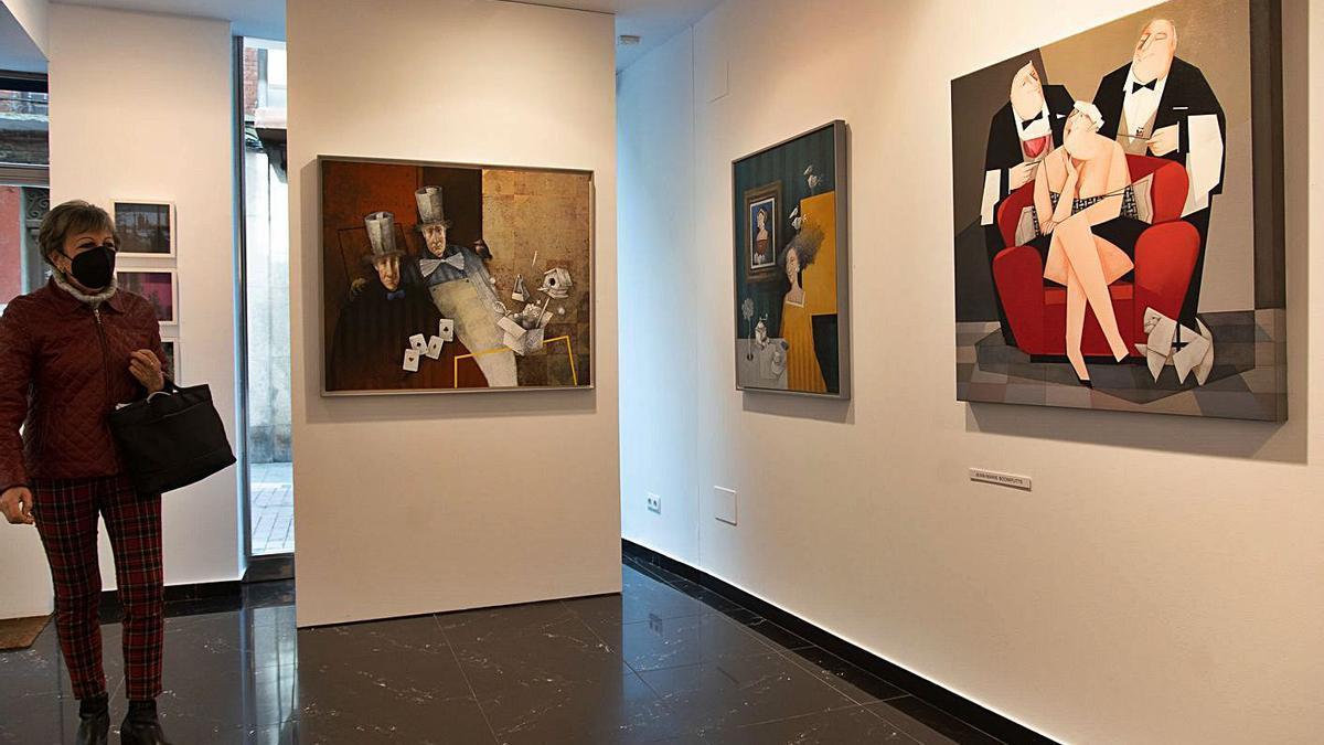 Una visitante observa los cuadros de Manuel López Herrera y Jean-Marie Boomputte. | Jose Luis Fernández