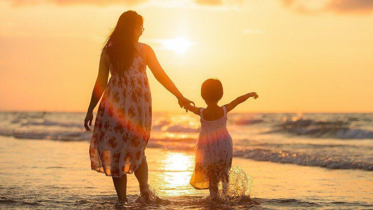 Una mujer y su hija pasean por la orilla en la playa.