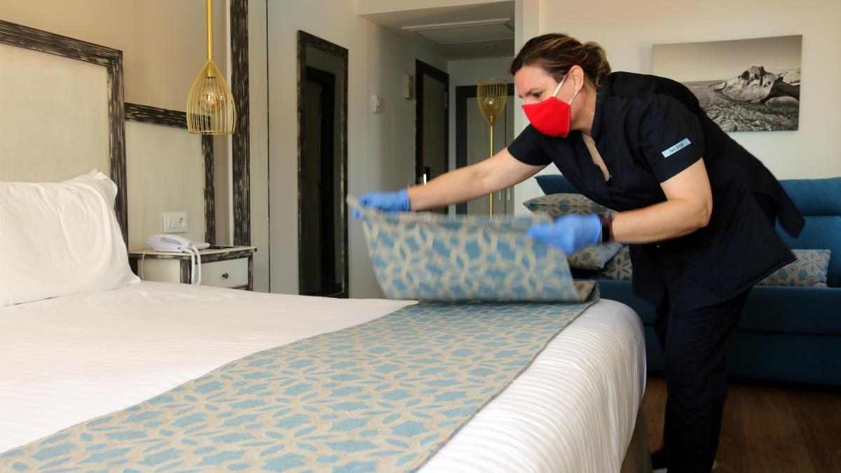 Una treballadora traient el plaid decoratiu del llit d'una habitació.