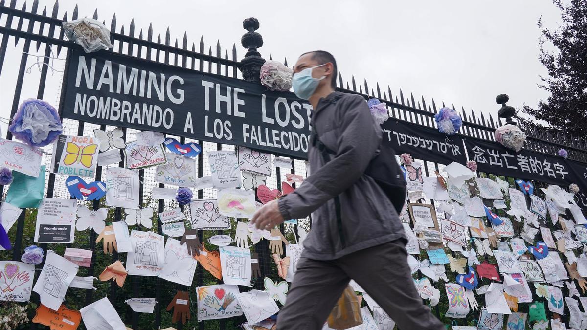Un hombre con mascarilla junto a un memorial en recuerdo a los fallecidos por coronavirus en EEUU