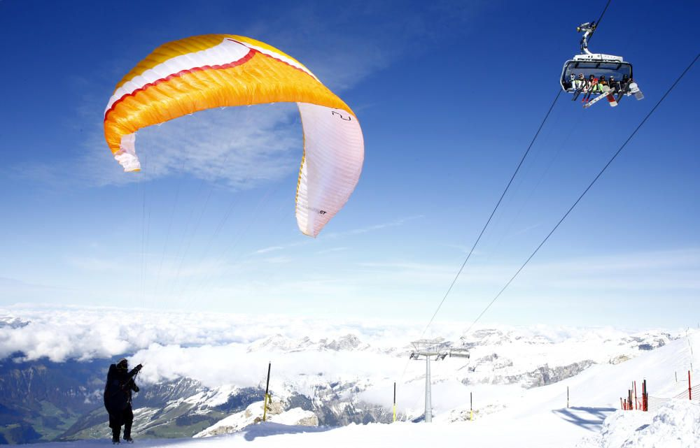 Paraglider prepares to start as skiers sit in a ...