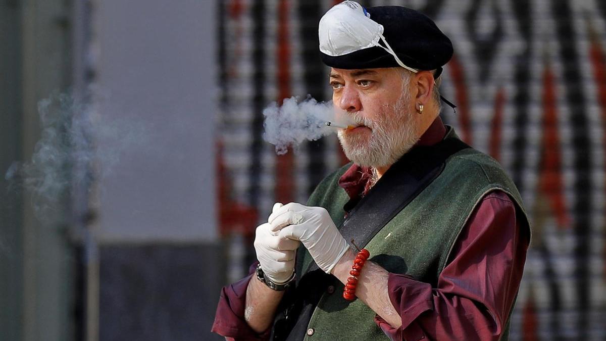 Un hombre se retira la mascarilla para fumar.