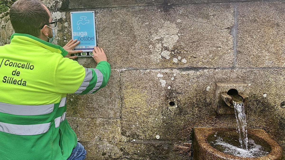 Un operario coloca un cartel de  agua potable en la fuente de  Arcos, en la parroquia de Graba.