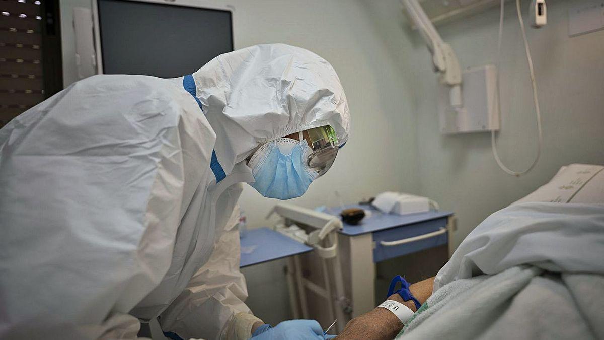 Una sanitaria atendiendo a un paciente covid-19 durante la segunda ola.