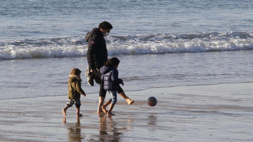 Un hombre juega con dos niños ayer en Samil