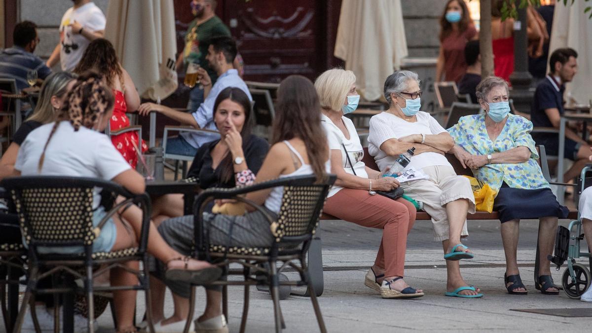 Una terraza de bar y un grupo de mujeres sentada en un banco en una imagen de archivo.
