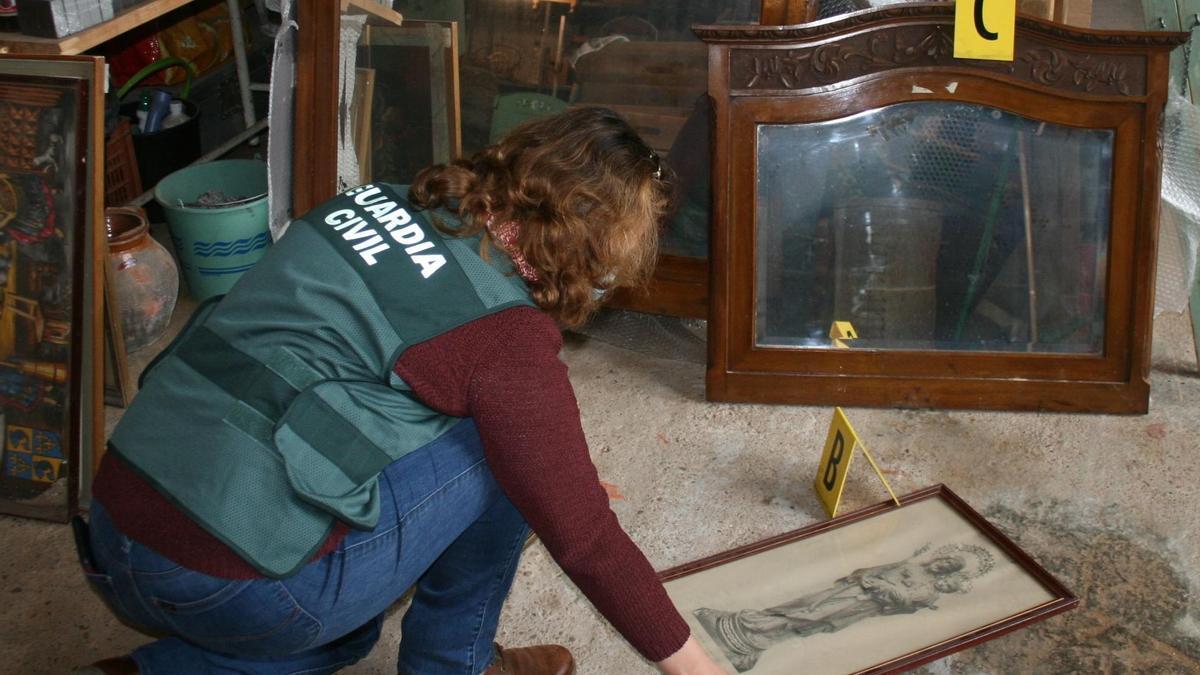 Una agente cataloga todos los muebles antiguos recuperados.