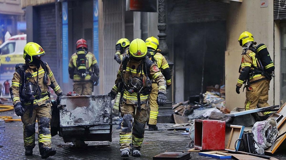 Los bomberos sacan muebles  del interior del local, que antes  estaba dedicado a la venta  de antigüedades.  Levante-EMV