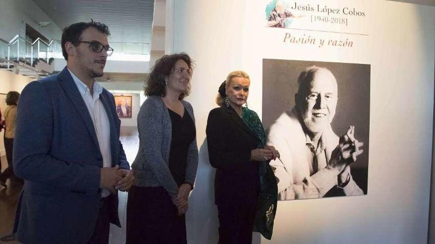 Del Bien, García Cirac y Brigitte, posan junto a un foto de López Cobos en la exposición .