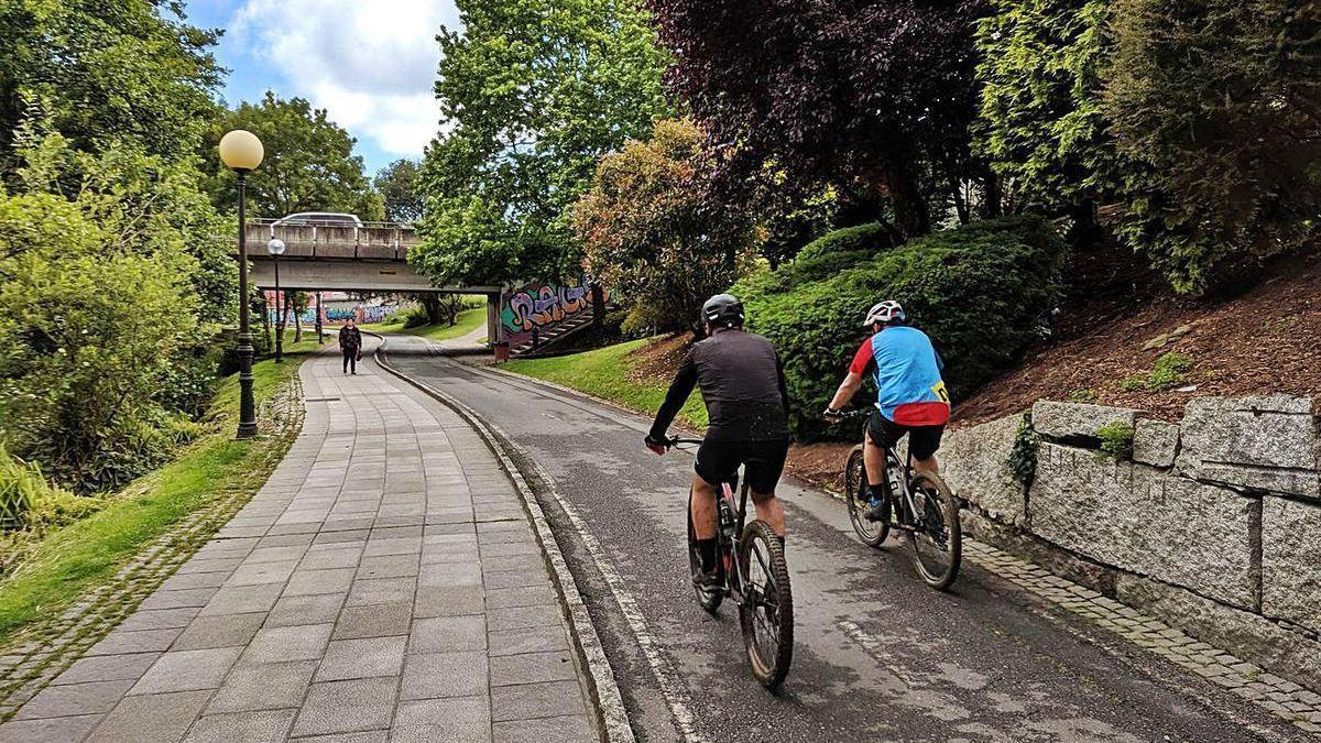 Dos ciclistas circulan por el paseo fluvial de Arteixo.