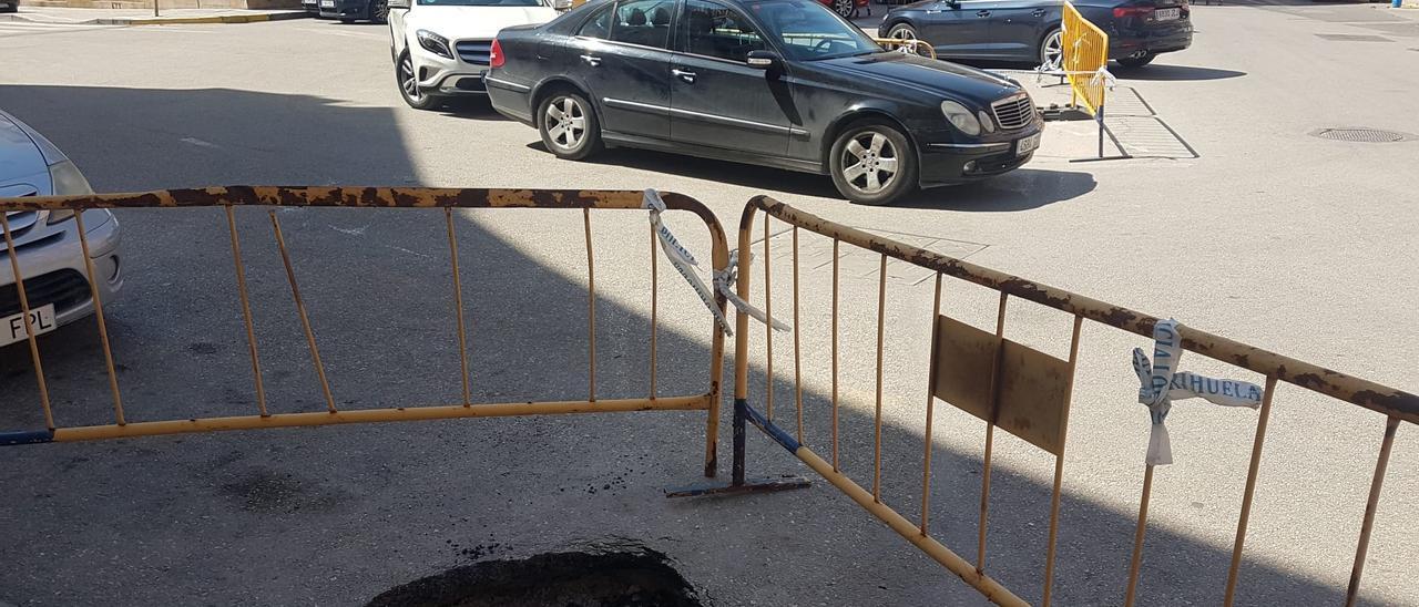 Socavón y, en el centro, los coches aparcan junto a las vallas en la calzada con riesgo de hundirse.