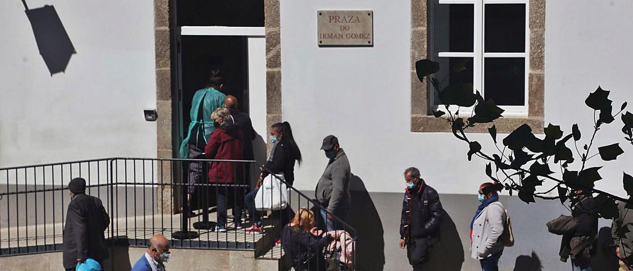 Un grupo de personas espera para poder comer en la Cocina Económica de Santiago.