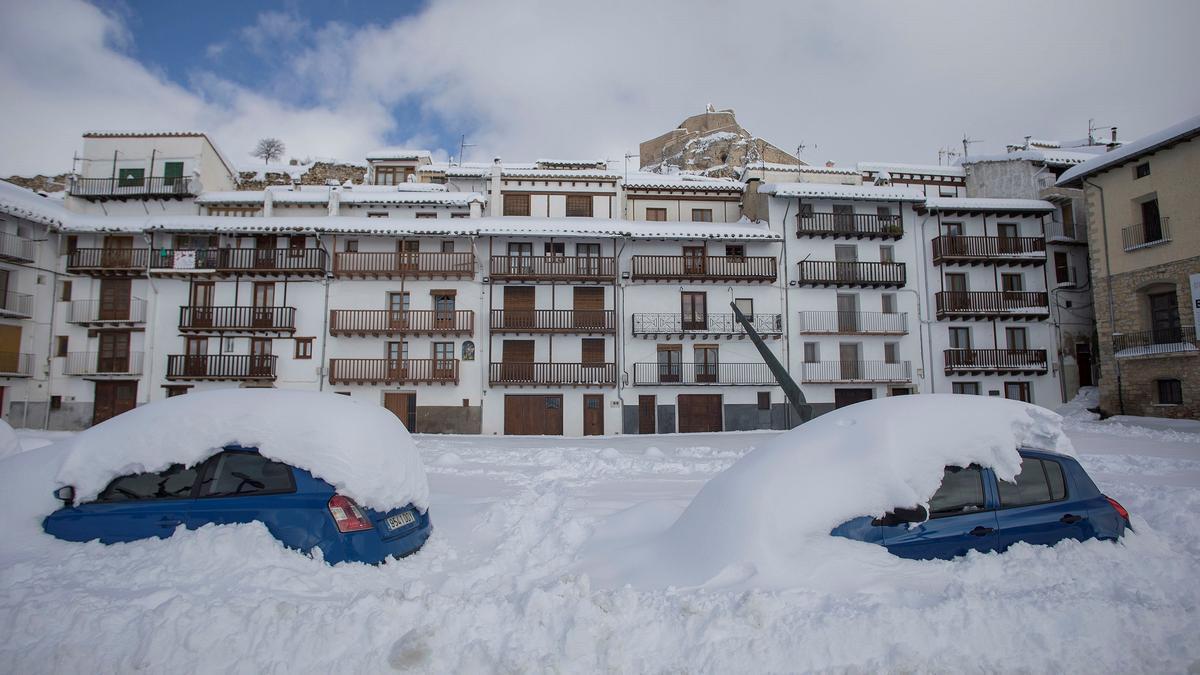 Aspecto de una plaza de Morella, con dos coches cubiertos de nieve durante el temporal 'Filomena'.