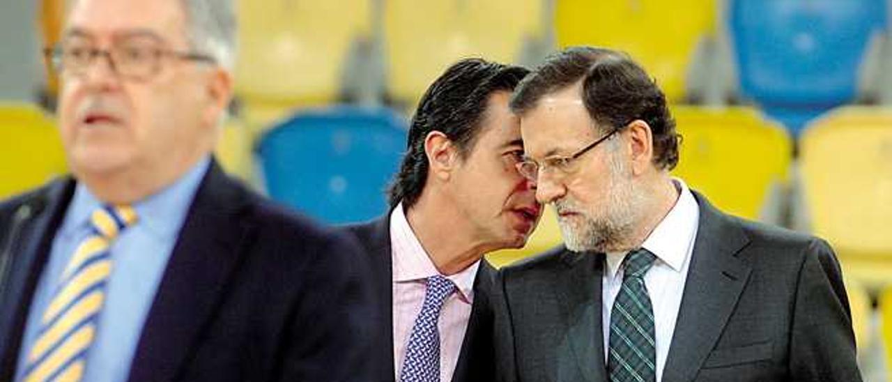 Imagen del 15 de marzo de 2014; José Manuel Soria habla al oído de Mariano Rajoy, mientras en primer plano, está José Miguel Bravo de Laguna.