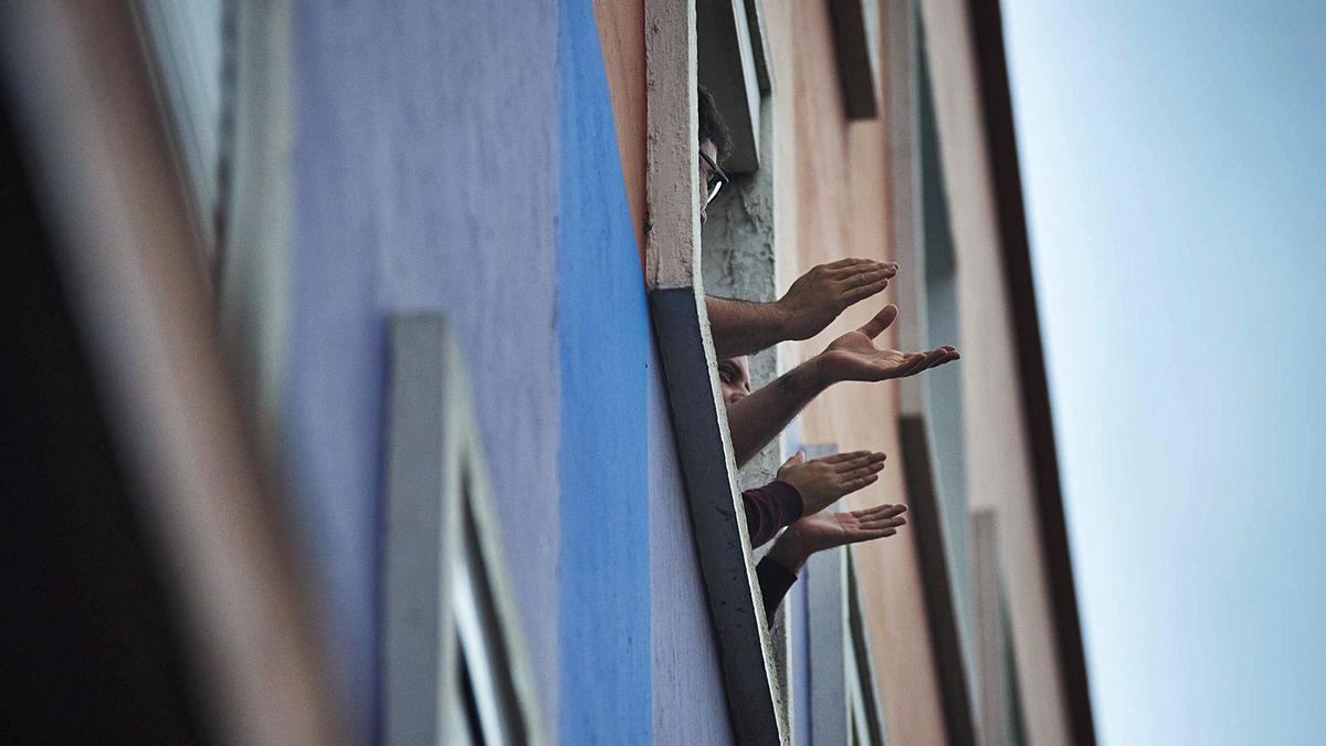Dos hombres salen a la ventana de su piso para aplaudir por los sanitarios durante el confinamiento de marzo de 2020.
