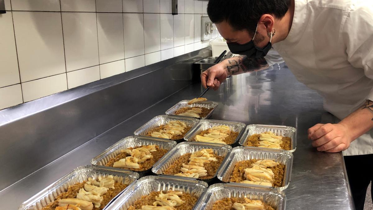Un xef preparant diversos dels plats que el seu restaurant serveix a domicili.