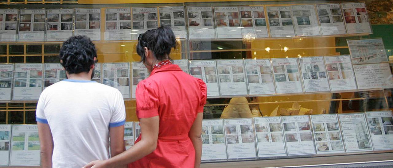 Dos jóvenes ante una inmobiliaria en Galicia // Casteleiro