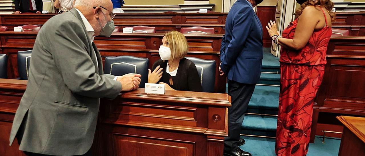 Noemí Santana, sentada, habla con Manuel Marrero (Podemos) mientras el consejero Julio Pérez charla con la diputada de CC, Cristina Valido, en un pleno. | | MARÍA PISACA