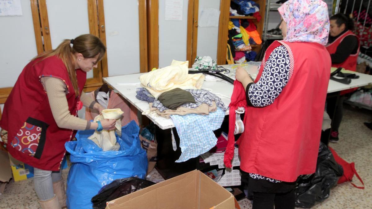 Una voluntaria reparte ropa en Cáritas Cartagena.