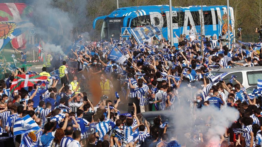 Aficionados de la Real Sociedad despiden al autobús del equipo.