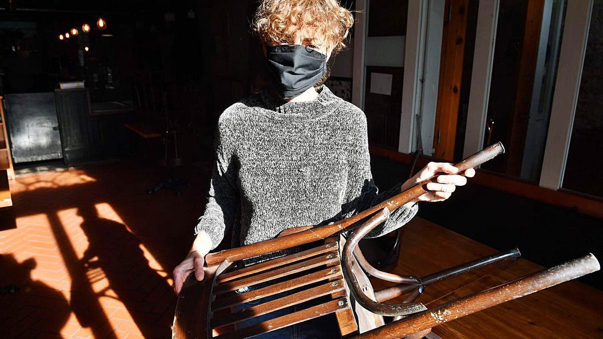 Ana Silva, ayer, en el Valentín, recoge una silla.   | // VÍCTOR ECHAVE