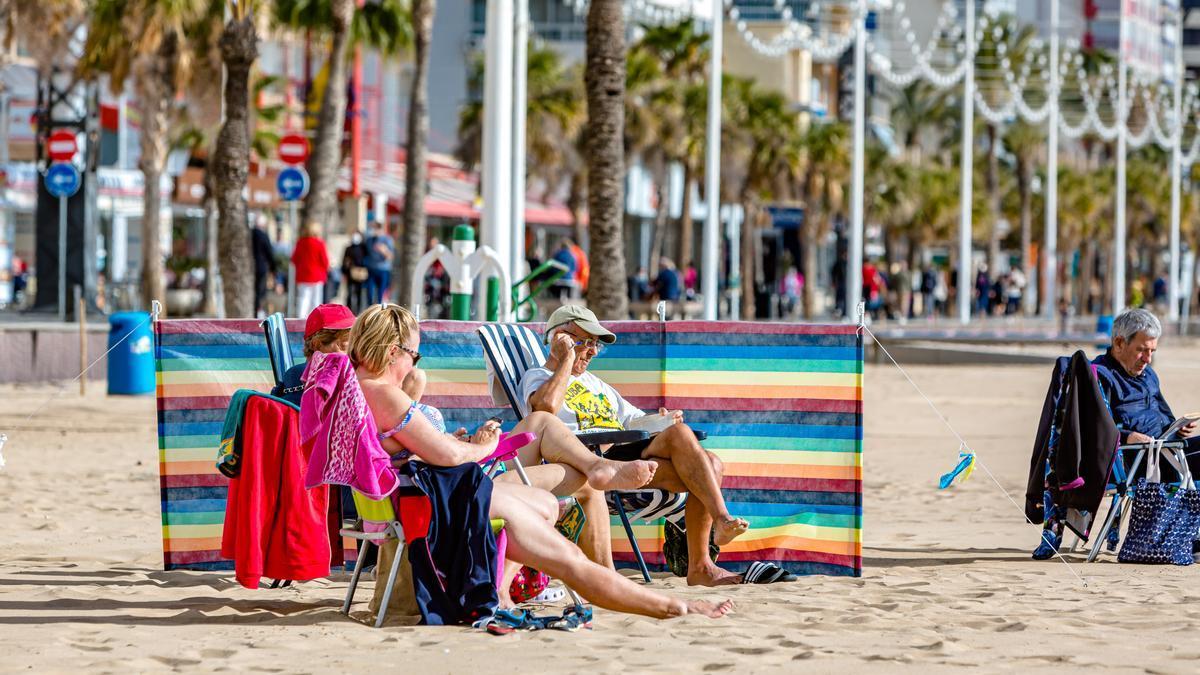 Turistas al tibio sol de enero en la playa de Levante de Benidorm