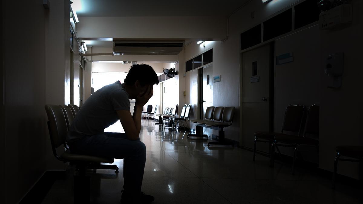 Un joven llora sentado en un hospital