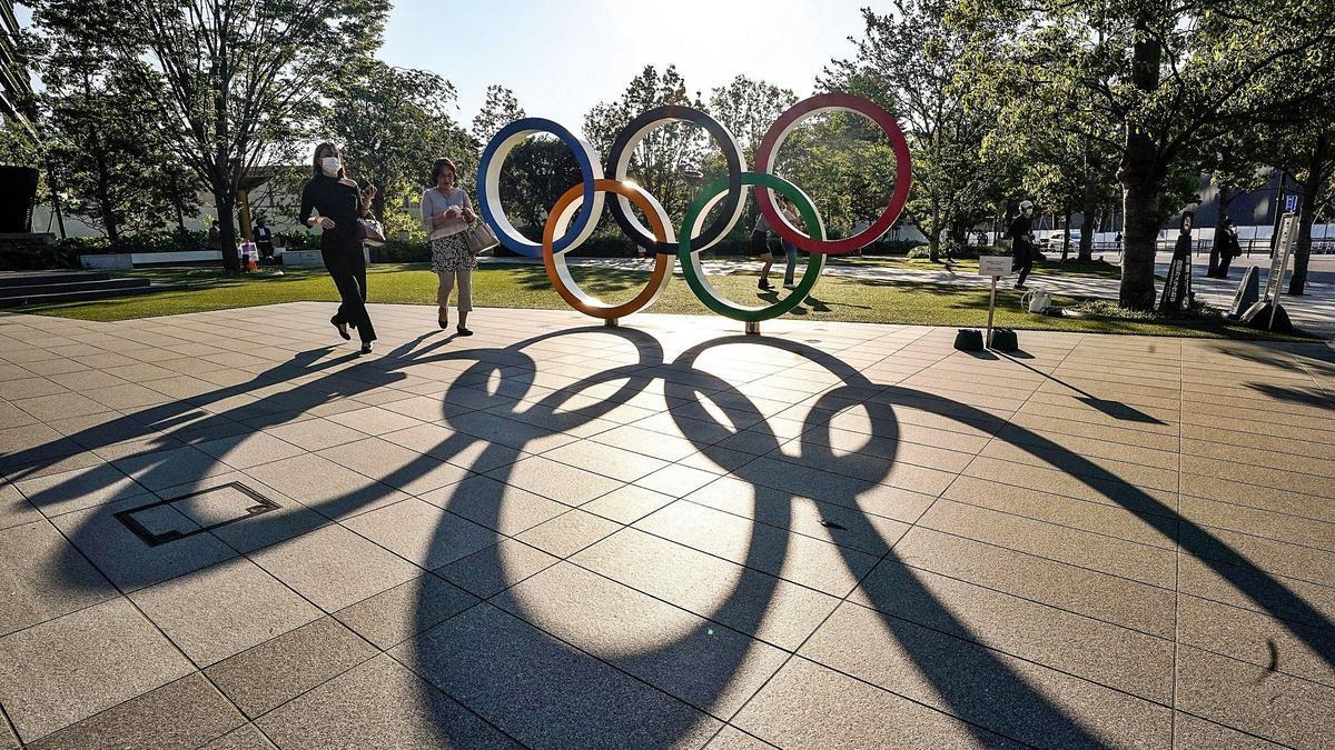 Dos mujeres pasean frente a los aros que están junto al Estadio Olìmpico de Tokio. | EFE/KIMIMASA MAYAMA