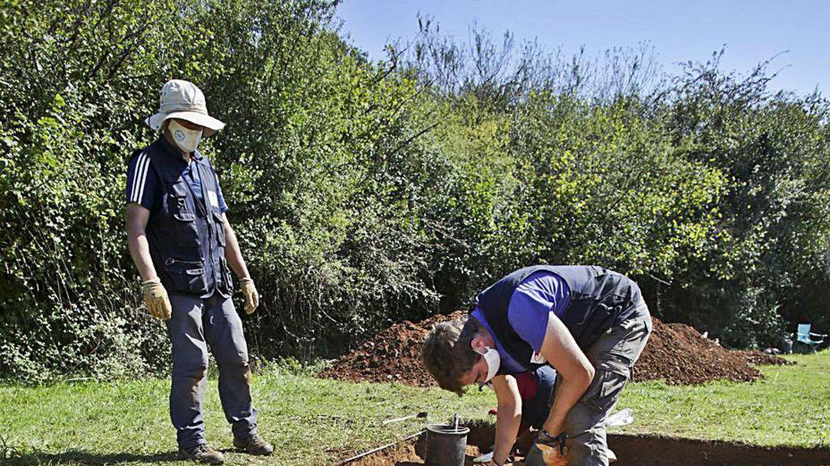 Juan Muñiz, a la izquierda, y Adrián Piñán, ayer, excavando en la construcción descubierta a 25 metros del edificio central de la villa romana.