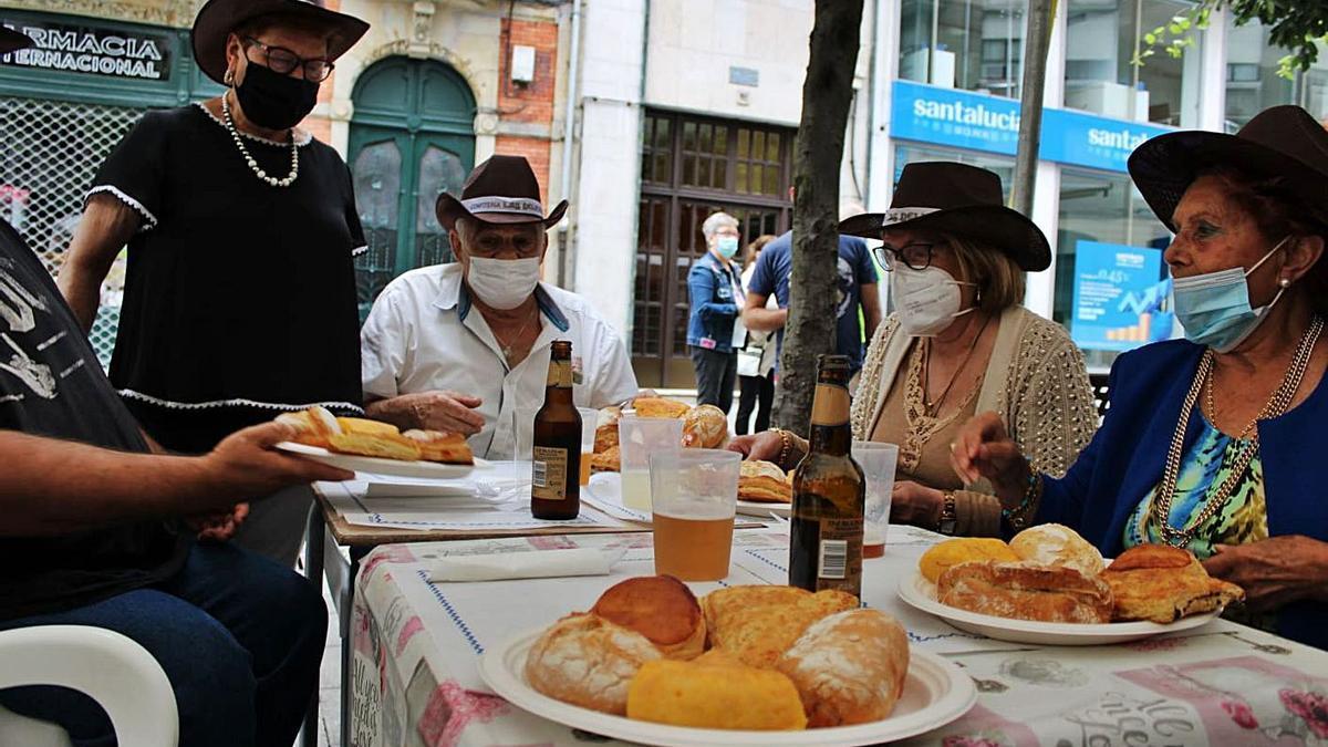 Varios romeros disfrutan del bollu, la empanada y la tortilla, ayer, en Sama.   L. M. D.