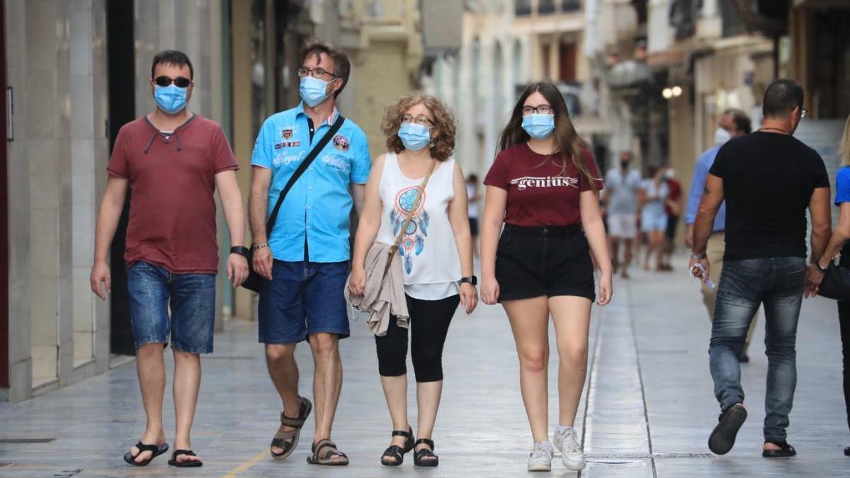 Personas con mascarilla caminan por una calle de Cartagena.