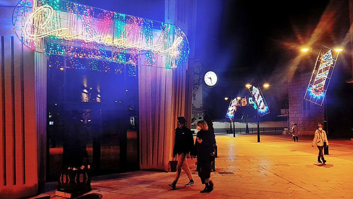 Peatones, ayer, paseando junto a las luces de Carnaval colocadas en torno al Auditorio.   LNE