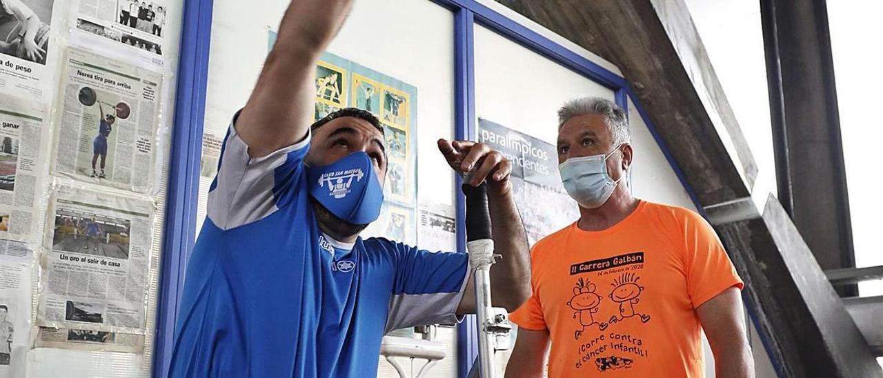 Miguel Menéndez, lanzando en el gimnasio San Mateo, en Oviedo, junto a su entrenador, Lodario Román.   Luisma Murias