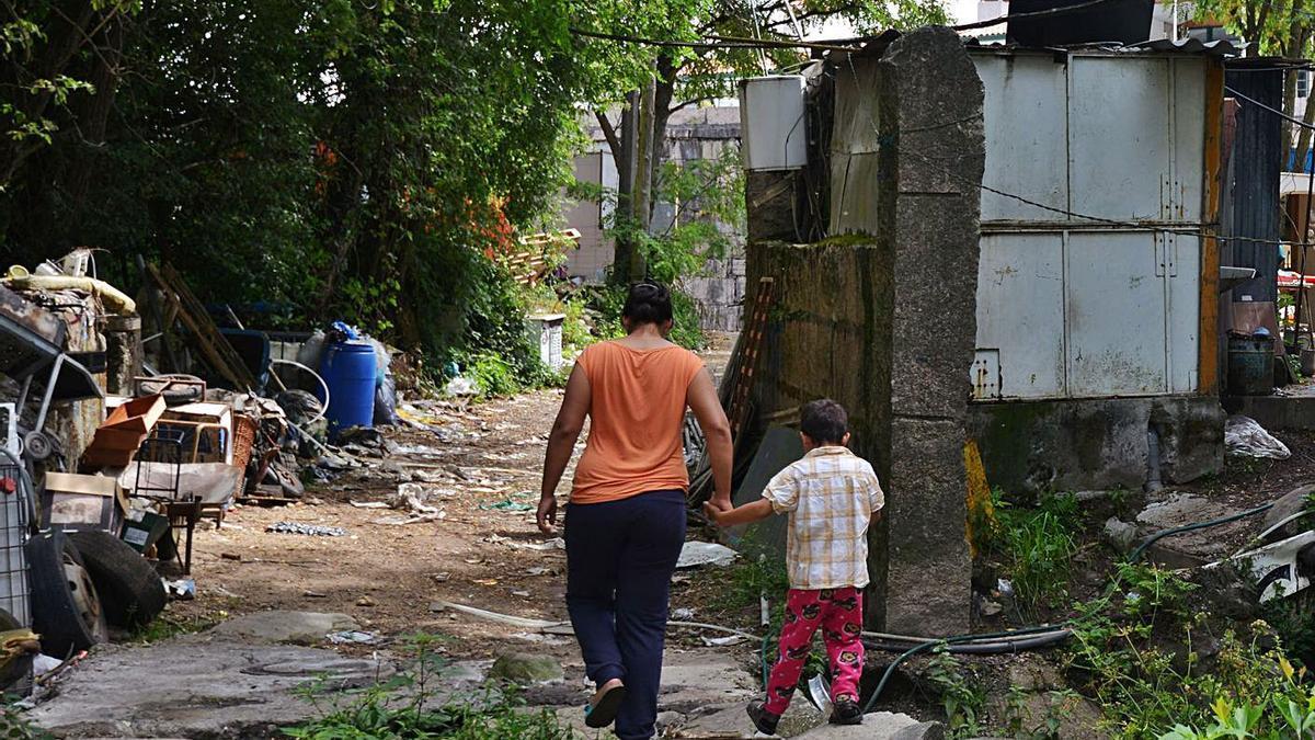Una madre camina con su hijo en un poblado chabolista de Pontevedra. |  // GUSTAVO SANTOS